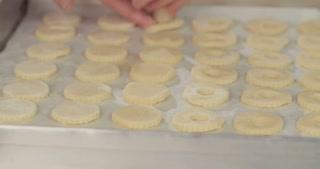 Baker cutting butter cookies using a cookie cutter