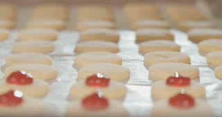 Baker piping strawberry jam on butter cookies