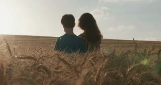 boy and girl hugging in a golden wheat field