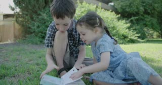 Boy and his young sister reading a childrens book on the grass
