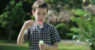 Boy blowing soap bubbles in the sun