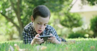 Boy laying on the grass holding a mobile phone