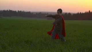 Boy with superhero cape running in a field during sunset