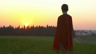 Boy with superhero cape standing in a field during sunset