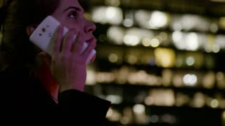 Business woman talking on the mobile phone at night