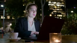 Business woman working on a laptop computer at night
