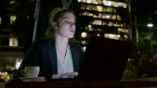 Business woman working with a laptop computer at night