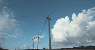 Clean energy - Wind turbine rotating with clouds in the background
