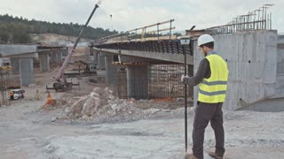 Construction engineer supervising a large road construction site using measurement instruments