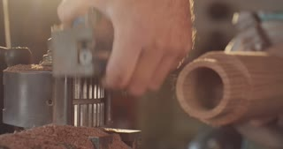 Craftsman creating wood art objects using a lathe