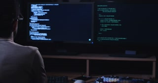 Cyber terror - computer hacker sitting in a dark room in front of screens and hacking systems