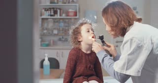 Doctor checking the throat of a little girl