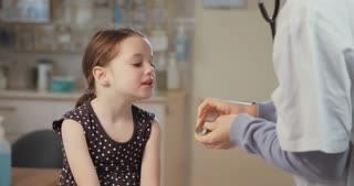 Doctor using stethoscope to check a cute little girl