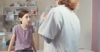 Doctor using stethoscope to check a young girl