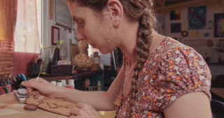 Female artist decorating a Buddhist prayer wheel using small brush and colors