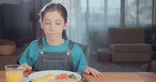 girl drinking orange juice during breakfast