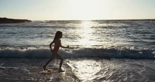 Girl running happy on the beach during sunset