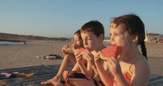 Kids eating watermelons on the beach during sunset