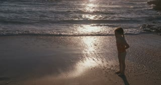 Little girl and her mother hugging at the beach during sunset