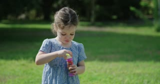 Little girl blowing soap bubbles in the sun
