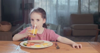 Little girl drinking orange juice during breakfast