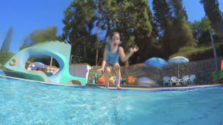 Little girl jumping and playing in a swimming pool