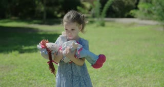 Little girl playing with a doll outdoors