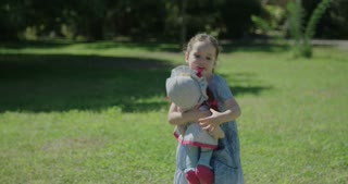 Little girl playing with her doll outdoors