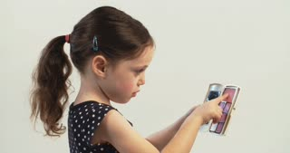 Little girl putting on makeup on a white studio background
