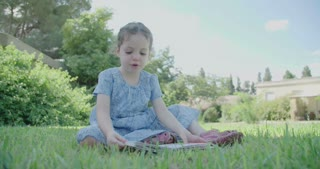 Little girl sitting on the grass reading a children's book