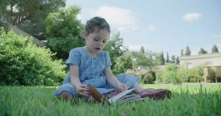 Little girl sitting on the lawn reading a children's book