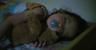 Little girl sleeping hugging a teddy bear