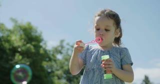 Little girl wearing a blue dress blowing soap bubbles