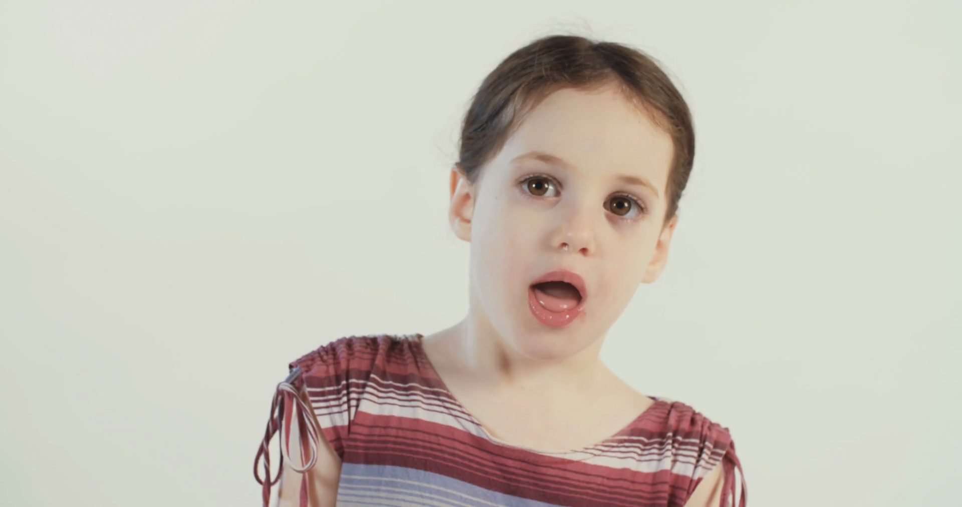 Little girl wearing a dress pulling out tongue Stock Video