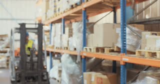 Logistics worker driving a forklift in a warehouse, and inspecting items