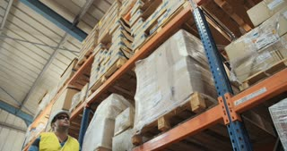 Low angle tracking shot of a logistics worker walking in a large warehouse