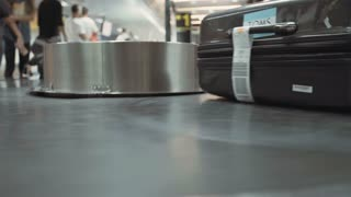Luggage on a conveyor at the airport. People picking up luggage