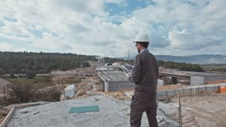 Man flying a drone to inspect a large construction project