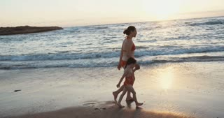 Mother and daughter running on the beach during sunset