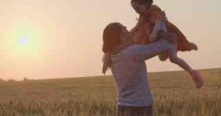 Mother and her young daughter walking and playing in a field of wheat during sunset