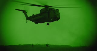 Night vision footage of Military helicopter in a rescue mission - soldier using rope to rescue injured man