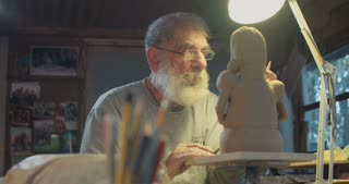 Old artist working on a clay sculpture in a small studio