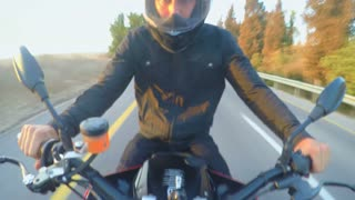 POV shot from a sport motorcycle driving at high speed on a curved countryside road