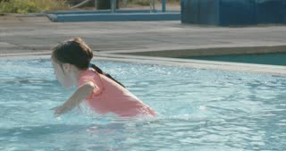 Slow motion shot of a little girl playing in a swimming pool