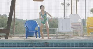 Slow motion shot of a young girl jumping to a swimming pool