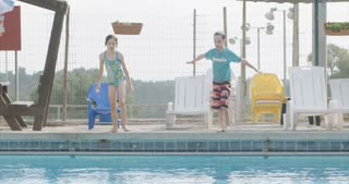 Slow motion shot of young kids jumping to a swimming pool