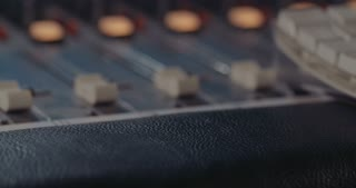 sound engineer working with a mixing console and microphones in a recording studio