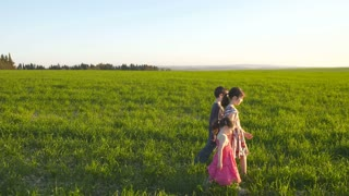 Steadicam shot of three young kids running in a green field during sunset