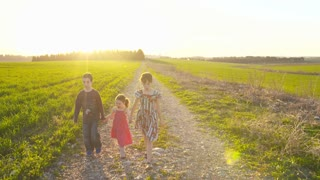 Steadicam shot of three young kids walking in a green field during sunset