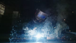 Super slow motion footage of a man welding metal parts in a workshop
